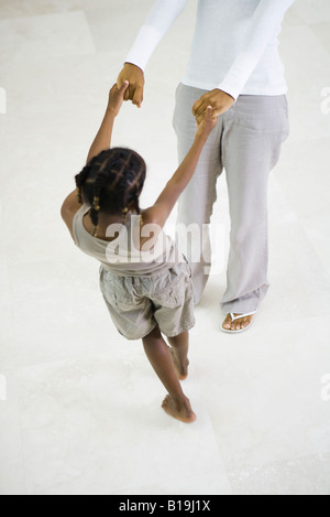 Little girl dancing, holding mother's hands, cropped view - Stockfoto