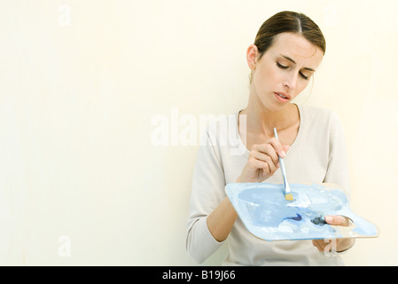 Woman holding artist's palette and paintbrush - Stock Photo