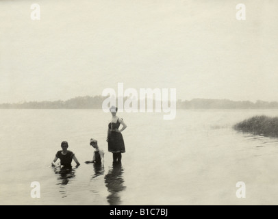 Antique photograph, circa 1890s, of two women and 1 man dressed in Victorian-era bathing suits swimming in a New - Stockfoto
