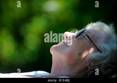 A  BRITISH OLD  LADY PENSIONER ENJOYS A SUNNY DAY SUNBATHING SLEEPING IN RETIREMENT RELAXING CONTENT,UK,ENGLAND. - Stockfoto