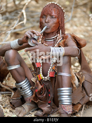 A Hamar woman blows a tin trumpet at a 'Jumping of the Bull' ceremony. The Hamar are semi-nomadic pastoralists. - Stock Photo