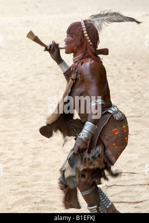 An old Hamar woman dances and blows a trumpet at a 'Jumping of the Bull' ceremony. The Hamar are semi-nomadic pastoralists. - Stock Photo