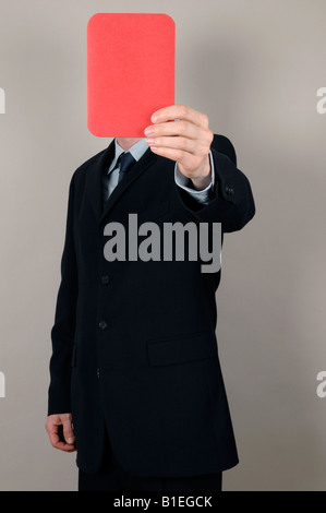 Businessman holding a red card in front of face - Stock Photo