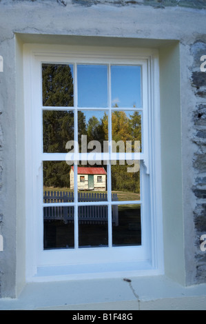 Reflection of Old Shed in window of Skippers School Skippers Canyon near Queenstown Central Otago South Island New - Stock Photo