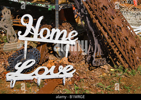 Metal garden decorations of words Love and Home next to rusted metal objects - Stock Photo