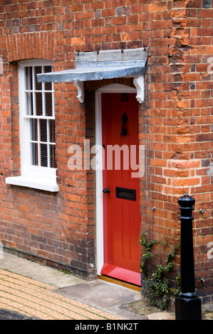 Pretty Red Painted Brick House With Window Boxes Full Of