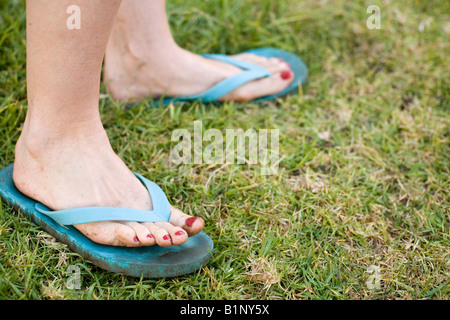 woman's feet and toes covered in dirt from garden work in blue sandals on lawn with red painted toenails - Stock Photo