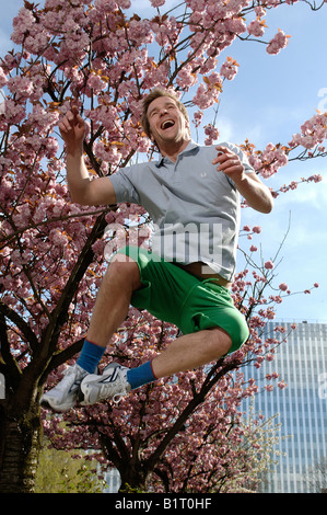 33 year-old man jumping in the city in spring - Stock Photo