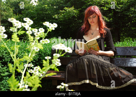 fairy tale girl reading Alice in Wonderland seated on a park bench - Stockfoto