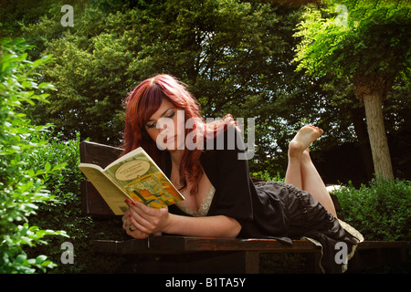 barefoot girl reading Alice in Wonderland seated on a park bench - Stockfoto