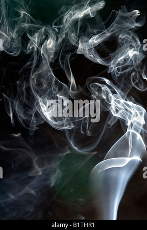 White smoke pattern from a burning incense stick against a black background. Part of it looks like an arum lily - Stock Photo