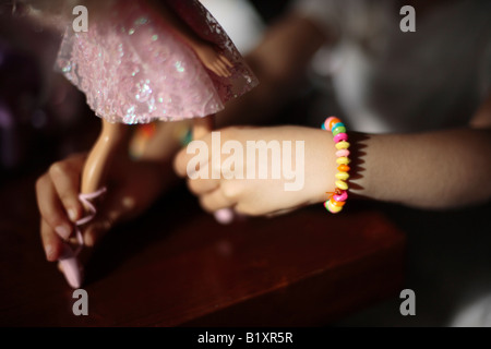 Girl aged five plays with her birthday presents, pink Barbie ballerina - Stock Photo