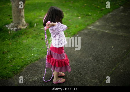 Girl aged four learning to skip Note trademarked Disney skipping rope - Stockfoto