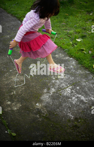 Girl aged four learning to skip - Stockfoto