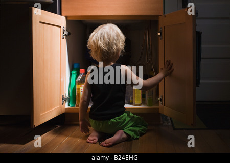 Little boy opening cupboard of cleaning products - Stock Photo