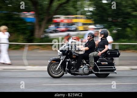couple rides a harley davidson motorbike in hamburg. Black Bedroom Furniture Sets. Home Design Ideas