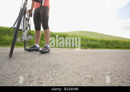 Cyclist with bike, low section - Stock Photo