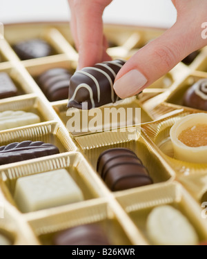 Woman holding chocolate over box of chocolates - Stock Photo