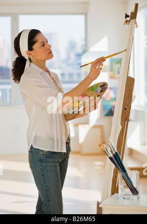 Hispanic woman painting on easel - Stockfoto