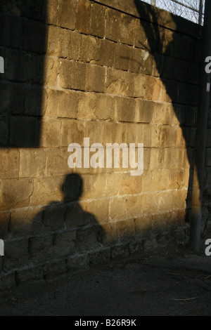 one man's shadow on wall in city town - Stock Photo
