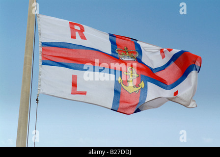 A closeup image of the RNLI flag in Newquay harbor flying in a strong wind shot in Cornwall England - Stock Photo