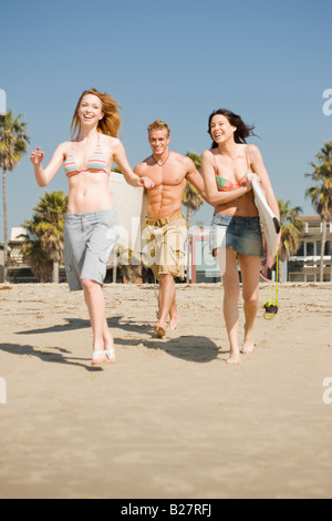 Friends carrying surfboards at beach - Stock Photo
