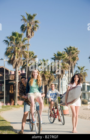 Friends with surfboard and bicycles at beach - Stock Photo