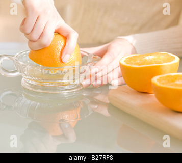 Woman squeezing oranges - Stock Photo