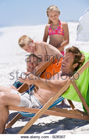 Family of four on beach, father taking photograph of himself in deck chair - Stock Photo