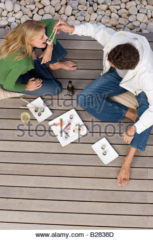 Young couple on decking, man feeding woman sushi with chopsticks, elevated view - Stockfoto