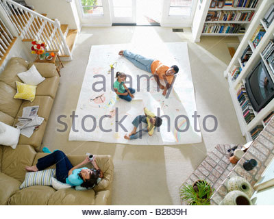 Family of four in living room, drawing on large piece of paper on floor, elevated view - Stock Photo