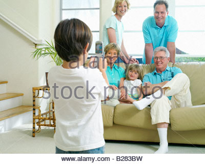 Boy (7-9) taking photograph with mobile phone of parents, grandparents and sister (6-8) on sofa, smiling - Stock Photo
