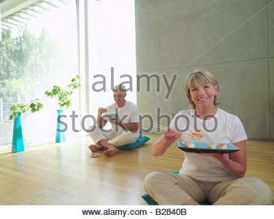 Mature couple on cushions, woman eating sushi with chopsticks, smiling, portrait - Stockfoto