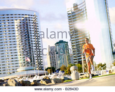 Young man running by skyscrapers, low angle view (sun flare) - Stock Photo