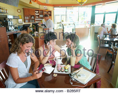 Young woman with friends in cafe, using mobile phones - Stock Photo