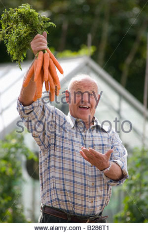 Senior man with carrots, smiling, portrait - Stock Photo