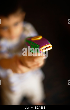 Boy takes aim with toy pistol Six year old mixed race indian ethnic and caucasian - Stock Photo