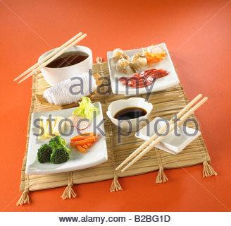 Asian food on mat with chopsticks - Stock Photo