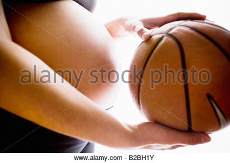 Close up of woman's pregnant stomach and a basketball - Stock Photo