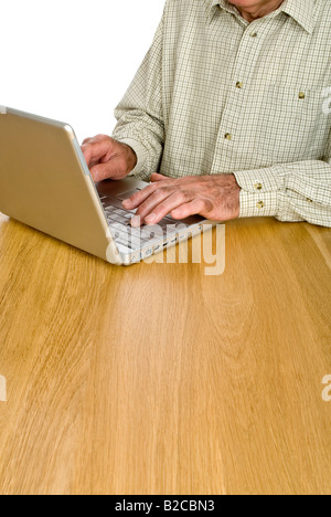 Vertical portrait of an elderly gentleman surfing the internet on his laptop computer against a white background - Stock Photo
