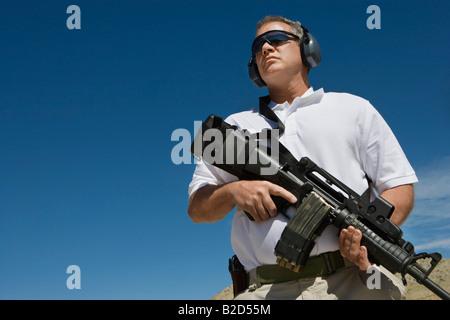 Man holding machine gun at firing range, low angle view - Stock Photo