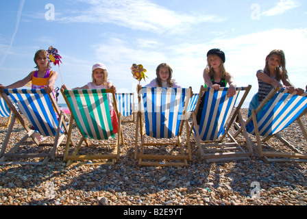 Kids sitting on striped sunloungers at the beach - Stock Photo
