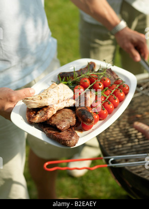 Close-up of person's hand holding sausages and cherry tomatoes on plate - Stock Photo