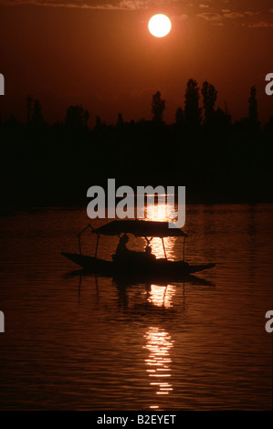 A couple floats in a shikara on Lake Dal in Srinagar India during sunset - Stock Photo