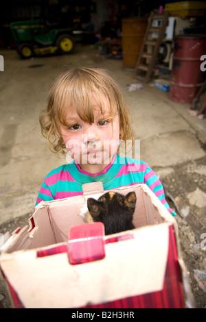 Young girl in rural Iowa, holding box of new kittens, Iowa, USA - Stockfoto
