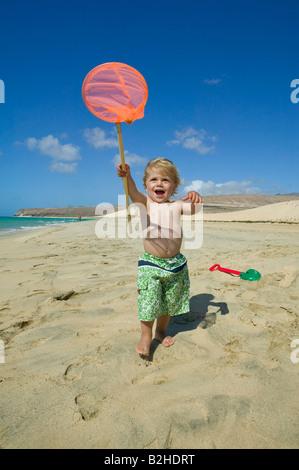 little boy walking along beach holding spoon net - Stock Photo