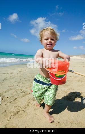 little boy walking on beach holding bucket - Stock Photo
