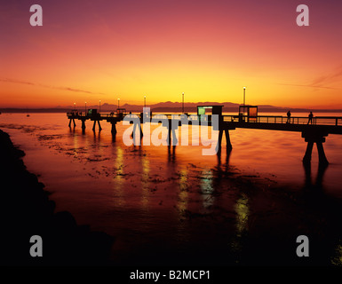 Silhouetted pier with people fishing off pier at sunset on Puget sound with Olympic mountains Edmonds Washington - Stockfoto