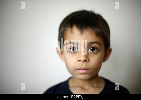Six year old boy mixed race indian ethnic Hands of father holding his face - Stock Photo