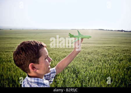 Boy playing with toy plane - Stockfoto
